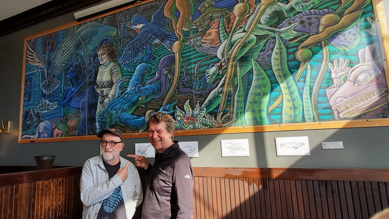 Artist Ray Troll, glasses, in front of his mural 'conversation' inside the New York Cafe with sea urchin diver Dave Rudie.