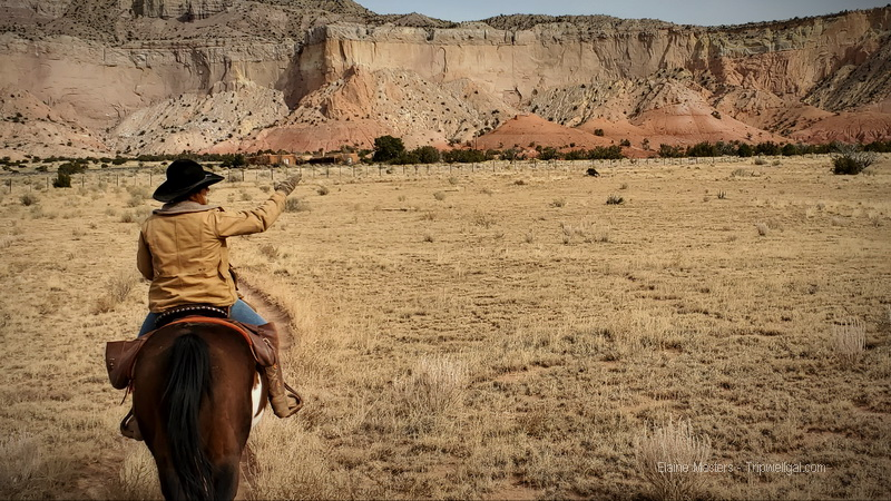 Trail ride guide points to O'Keeffe's home at Ghost Ranch